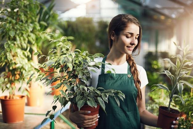 Giardiniere giovane imprenditore che gestisce il suo negozio di serra tenendo le piante in vaso.