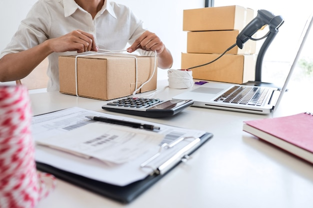 Il giovane imprenditore pmi riceve il cliente dell'ordine e lavora con il mercato online della consegna di scatole di smistamento degli imballaggi per l'ordine di acquisto e prepara il prodotto del pacco, pacchi di piccole imprese per la spedizione.