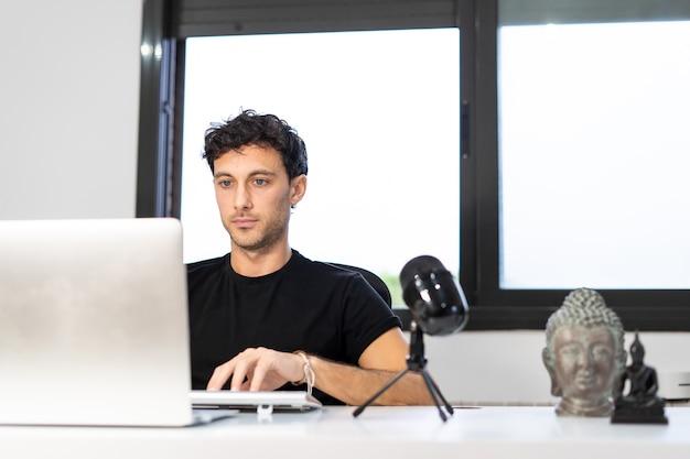 Il giovane imprenditore lavora da casa nel suo ufficio con il computer davanti a una finestra