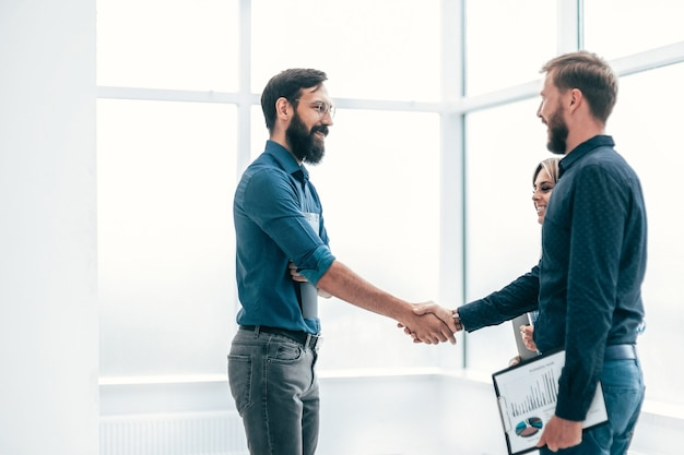 Giovani imprenditori che si stringono la mano a vicenda. concetto di cooperazione