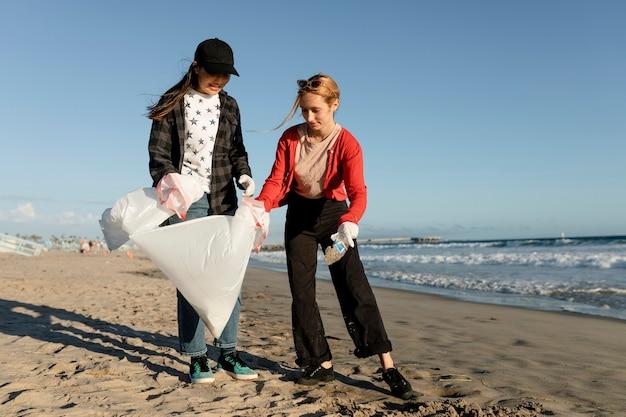 Giovani amici ambientalisti, volontariato per la pulizia della spiaggia