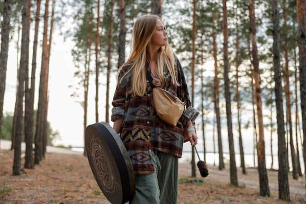 La giovane donna sciamana matura etnica sta camminando e suonando la musica meditativa della batteria