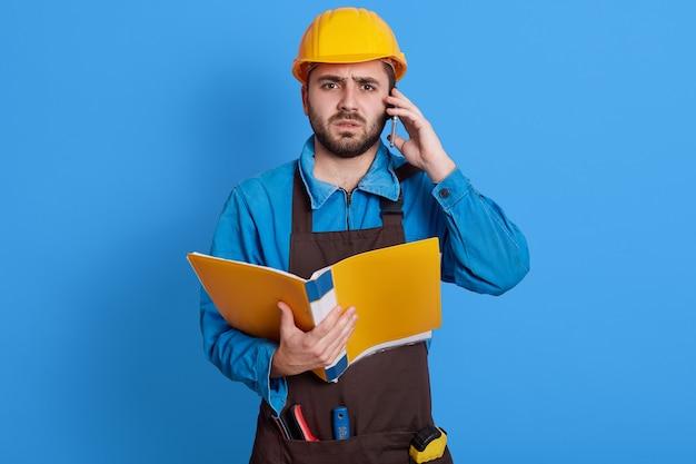 Giovane uomo barbuto europeo che lavora come architetto o caposquadra, risolve problemi di costruzione, tiene in mano una cartella di carta, parla al telefono, indossa grembiule, casco e uniforme blu.