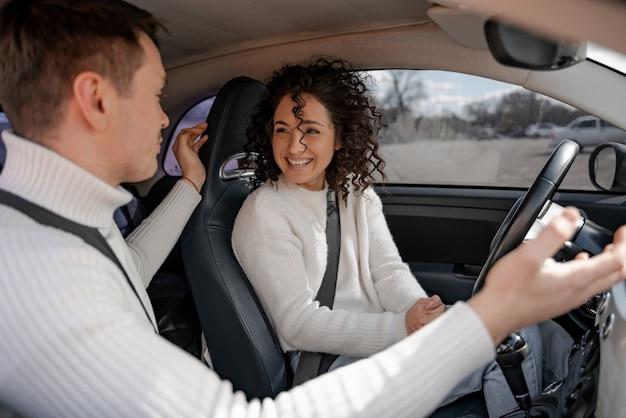 Giovani coppie europee che si siedono in macchina. uomo che gesticola con le mani e parla con una donna riccia. persone felici e sorridenti. donna moderna come autista. concetto di godersi il tempo insieme
