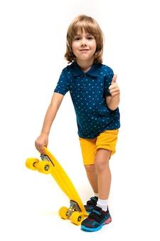 Il giovane ragazzo carino europeo in abbigliamento sportivo è in piedi e tiene in mano uno skateboard giallo su uno sfondo bianco.