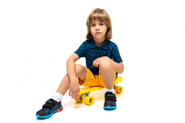 Giovane bambino sveglio europeo in abiti sportivi che si siedono sul pattino giallo su bianco