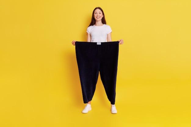 Giovane donna europea con i capelli scuri che indossa una maglietta bianca casual e pantaloni neri di taglia troppo grande, adorabile donna felice che perde peso, si sente benissimo, esprime positività, tiene le mani nei pantaloni.