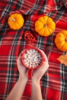 Giovane ragazza europea con il manicure rosso sulle unghie tiene in mano una tazza di caffè rosso con marshmallow