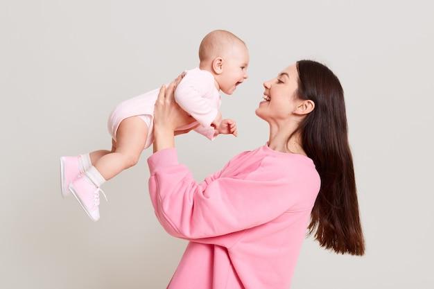 Giovane madre europea che tiene la sua bambina in mano e guarda il suo bambino con amore e sorriso gentile, femmina con i capelli scuri che indossa un maglione casual rosa, giocando con il suo bambino.