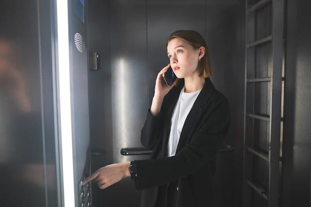 Il giovane impiegato europeo sta guardando il numero del piano nell'ascensore e sta parlando al telefono.