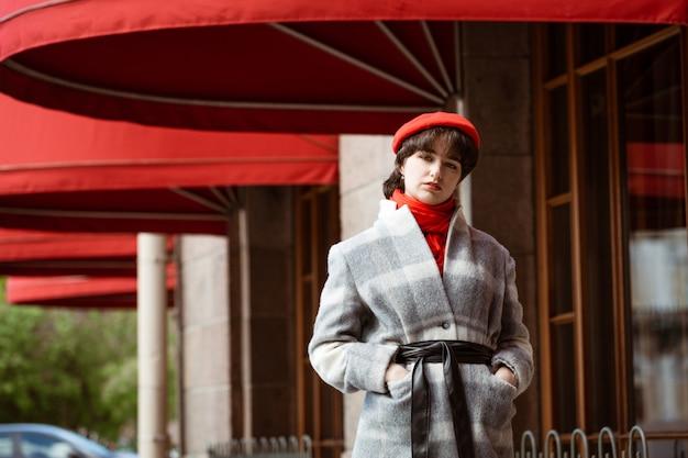 Giovane donna europea in cappotto grigio e sciarpa rossa all'aperto in una giornata di sole primaverile