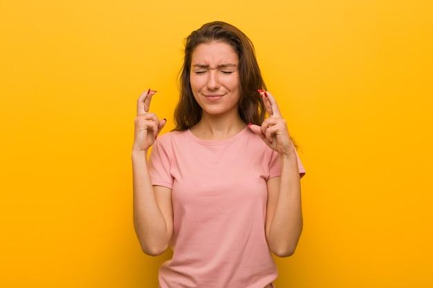 Giovane donna europea isolata sopra le dita incrocio muro giallo per avere fortuna