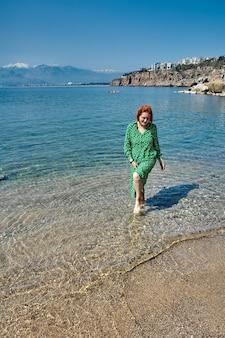 La giovane donna europea cammina a piedi nudi sulla spiaggia.