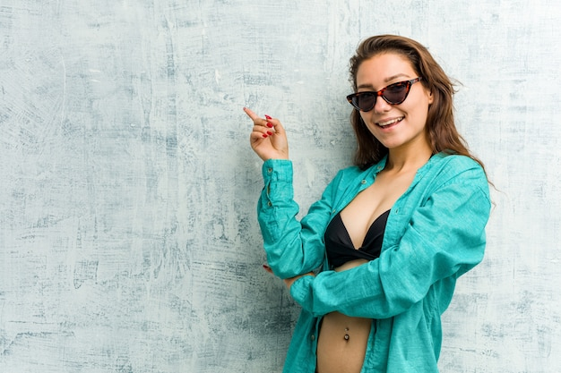 Bikini d'uso della giovane donna europea che sorride allegramente indicando con l'indice via