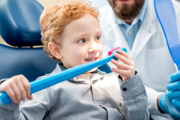 Giovane ragazzo eccitato seduto sulla sedia che tiene in mano un grande spazzolino da denti con il medico nello studio dentistico