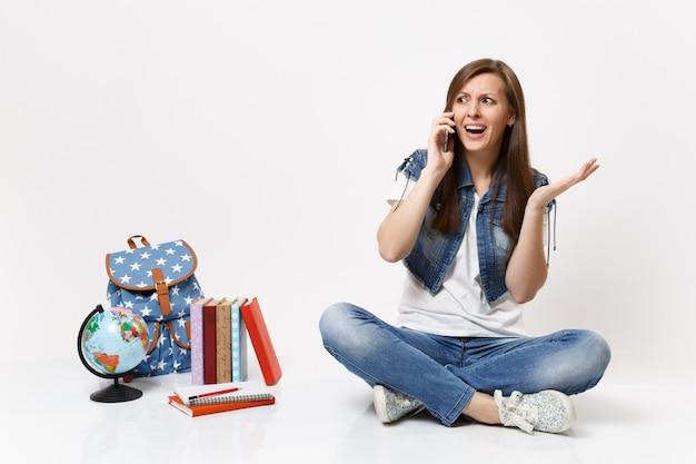 Giovane studentessa preoccupata eccitata che parla al telefono cellulare, allarga le mani e si siede vicino a globo, zaino, libri di scuola isolati su muro bianco