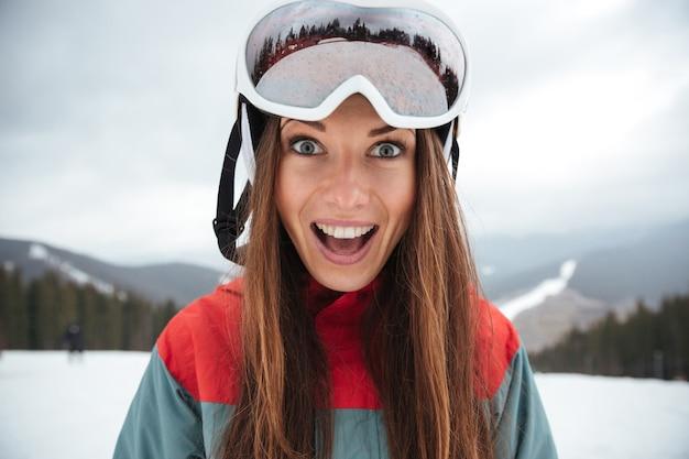Giovane snowboarder felice eccitato della signora sui pendii gelidi giorno di inverno