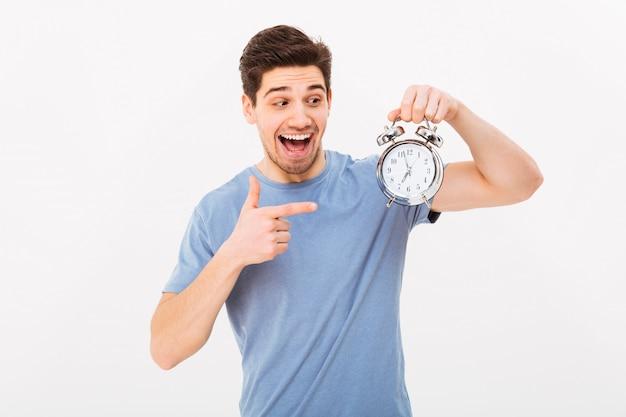 Giovane uomo emozionante in maglietta casuale e tenendo e indicando dito sulla sveglia, isolata sopra la parete bianca