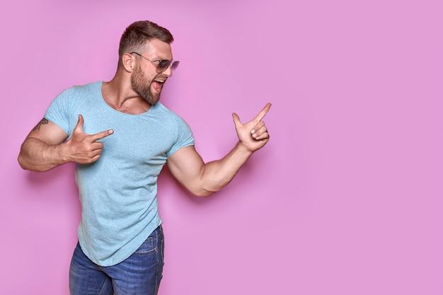 Giovane uomo eccitato in vacanza su sfondo rosa che punta il dito di lato con un'idea di successo