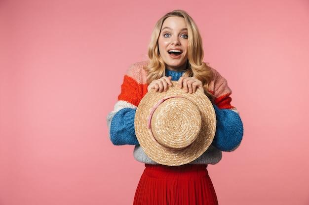 Giovane eccitata bella donna in posa isolata sul muro rosa che tiene il cappello