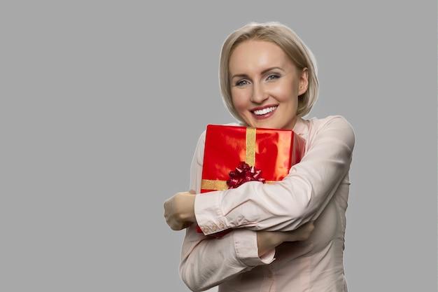 Giovane donna emozionante che tiene contenitore di regalo rosso. donna allegra con confezione regalo su sfondo grigio. concetto di regalo di compleanno.
