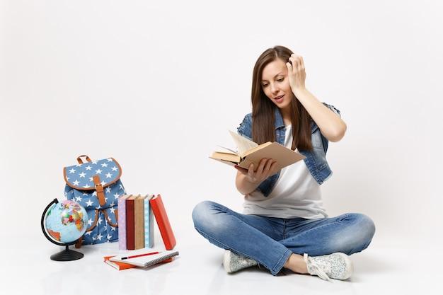 Giovane studentessa eccitata in abiti di jeans tiene il libro letto tenendo la mano vicino alla testa seduta vicino al globo, zaino, libri di scuola isolati su muro bianco