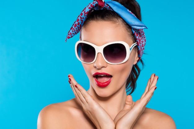 Giovane donna eccitata che indossa occhiali da sole e bandana rossa
