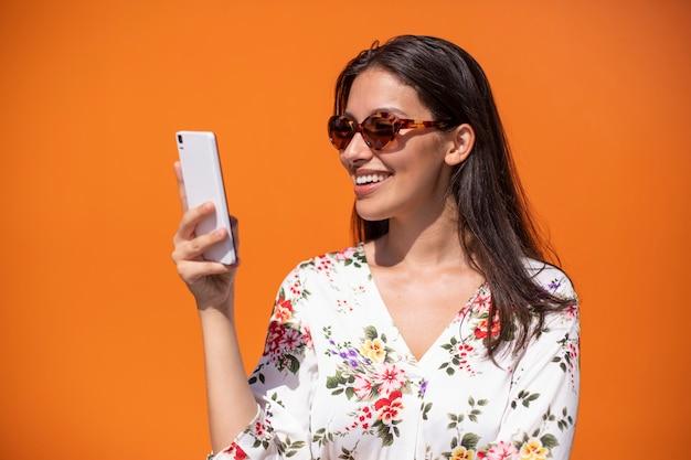 Giovane donna esecutiva che legge un messaggio sul telefono cellulare con fondo arancio