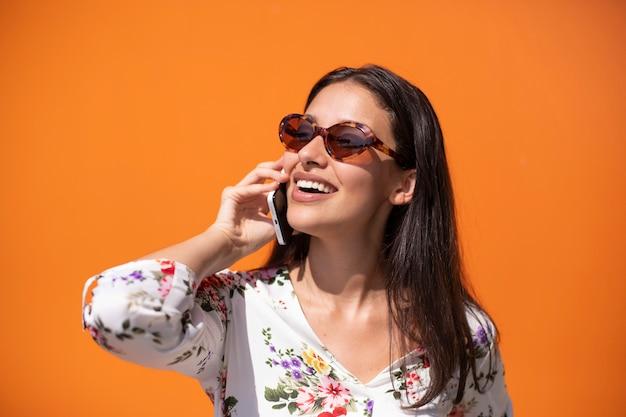 Giovane donna esecutiva che parla sul telefono con fondo arancio