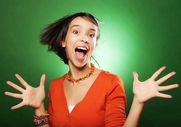 Giovane donna di espressione sulla parete verde
