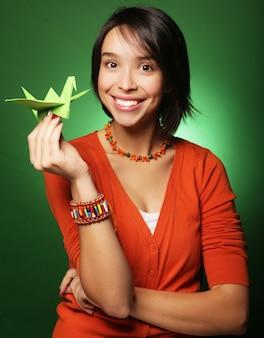 Giovane donna di espressione con uccello di carta su sfondo verde green