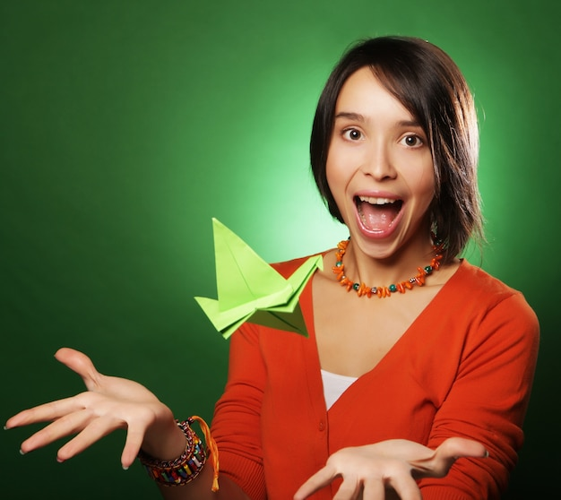 Donna giovane espressione con uccello di carta sopra la parete verde