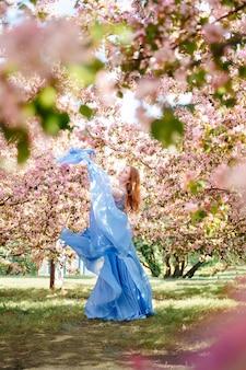 Una giovane ragazza delle fiabe in un morbido abito blu solleva il tessuto sullo sfondo di un a...