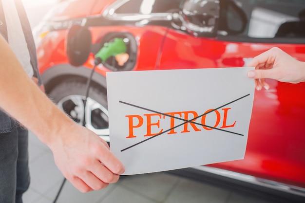 Giovane famiglia che acquista la prima auto elettrica nello showroom. niente benzina. primo piano delle mani che tengono la carta con la parola benzina sulla macchina elettrica della batteria.