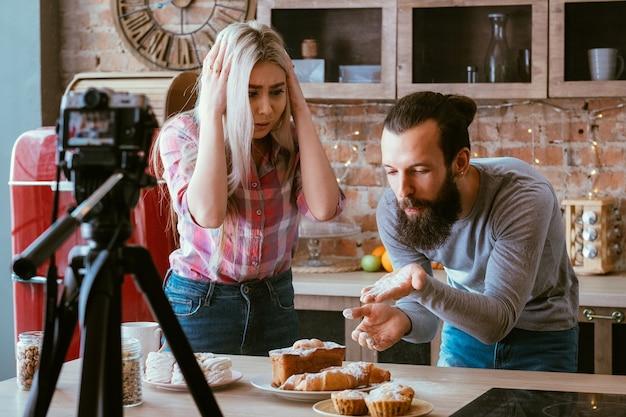 Cucina familiare giovane. passatempo di vlogging. panetteria fatta in casa. l'uomo spolvera i pasticcini con lo zucchero a velo
