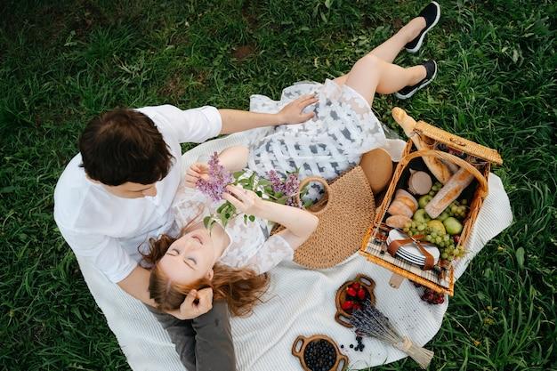 Una giovane coppia di famiglia sta riposando su un picnic sdraiato su una coperta leggera sul prato nel campo una passeggiata romantica per il marito e la moglie nel parco