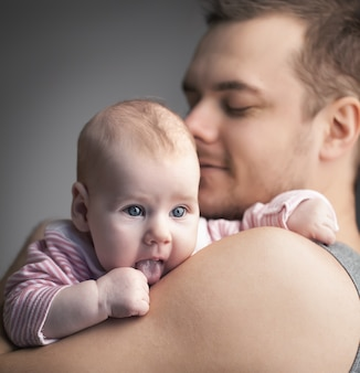 Famiglia giovane. il padre tiene la figlia per mano. l'uomo non si è rasato e sorride. bambina con la lingua fuori. foto a colori