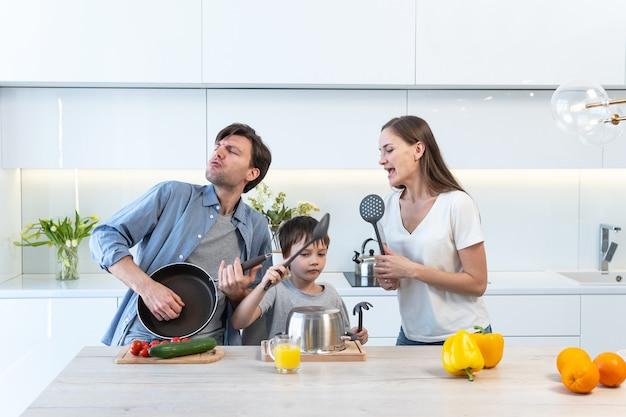 Giovane famiglia che si diverte, balla e canta in cucina