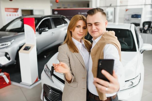 Giovane famiglia che fa selfie in uno show room di auto