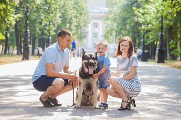 Giovane mamma, papà e figlio di famiglia in una passeggiata con un cane da pastore in città