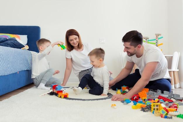 Giovane famiglia, mamma e papà con due figli piccoli, giocando con i giocattoli nella scuola materna, famiglia felice che si diverte insieme