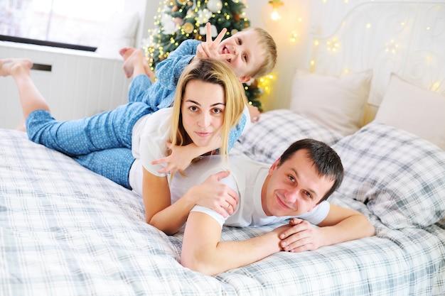 Giovane famiglia - madre, padre e figlio piccolo che abbracciano in pigiama sdraiato sul letto e sorridono sullo sfondo dell'albero di natale e della decorazione. celebrazione di natale.