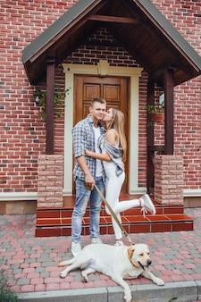 Giovane famiglia vicino a casa loro. coppie attraenti con labrador vicino alla grande casa.