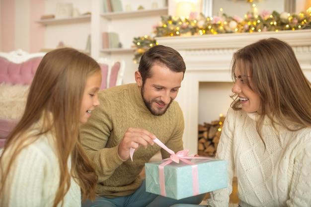 Giovane famiglia seduta sul pavimento e efeeling entusiasta dei regali di natale