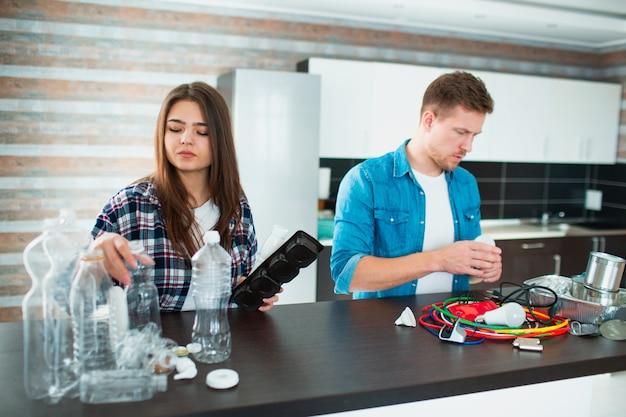 Una giovane famiglia ordina i materiali in cucina per il riciclaggio. i materiali riciclabili devono essere separati. la moglie ordina la plastica e il marito ordina i vecchi elettrodomestici, il vetro di ferro e altri rifiuti, i rifiuti