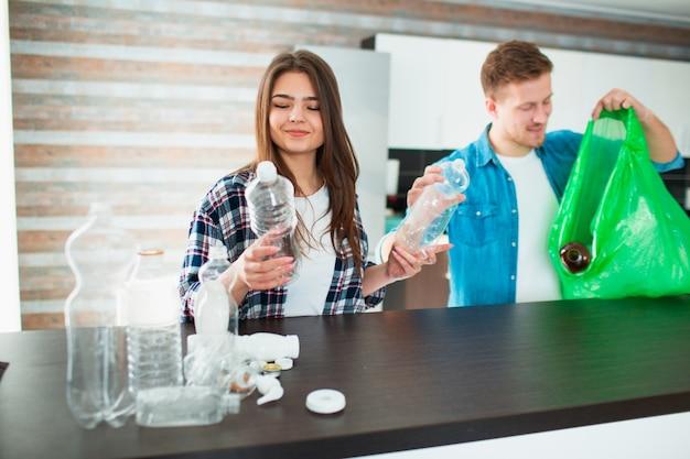 Una giovane famiglia ordina i materiali in cucina per il riciclaggio. i materiali riciclabili devono essere separati. la donna tiene in mano le bottiglie di plastica vuote e le dà all'uomo
