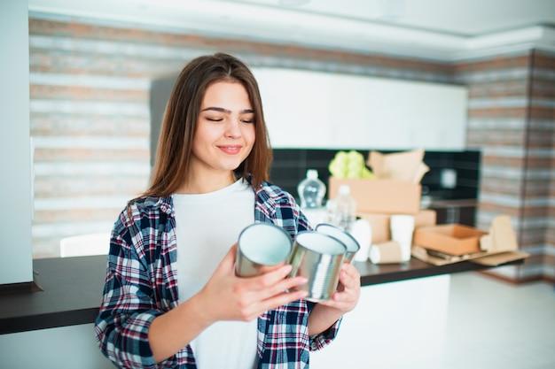 Una giovane famiglia ordina i materiali in cucina per il riciclaggio. i materiali riciclabili devono essere separati. giovane donna che tiene i vecchi barattoli di latta in sue mani per alimento. c'è spazzatura ordinata in background.