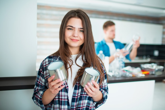 Una giovane famiglia ordina i materiali in cucina per il riciclaggio. i materiali riciclabili devono essere separati. giovane donna che tiene i vecchi barattoli di latta in sue mani per alimento. il giovane sullo sfondo ordina la spazzatura