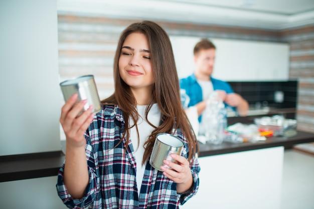 Una giovane famiglia ordina i materiali in cucina per il riciclaggio. giovane donna che tiene i vecchi barattoli di latta in sue mani per alimento. il giovane sul muro ordina la spazzatura