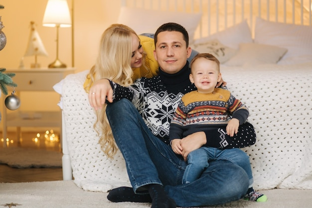 La giovane famiglia trascorre del tempo a casa nel periodo natalizio. mamma, papà e figlio felici godono di abbracci d'amore, persone in vacanza. concetto di solidarietà.